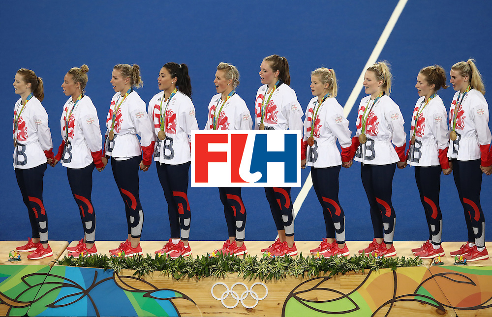 RIO DE JANEIRO, BRAZIL - AUGUST 19:  Team Great Britain look on from the podium as the national anthem plays during the medal ceremony after defeating Netherlands in the Women's Gold Medal Match on Day 14 of the Rio 2016 Olympic Games at the Olympic Hockey Centre on August 19, 2016 in Rio de Janeiro, Brazil.  (Photo by Mark Kolbe/Getty Images)