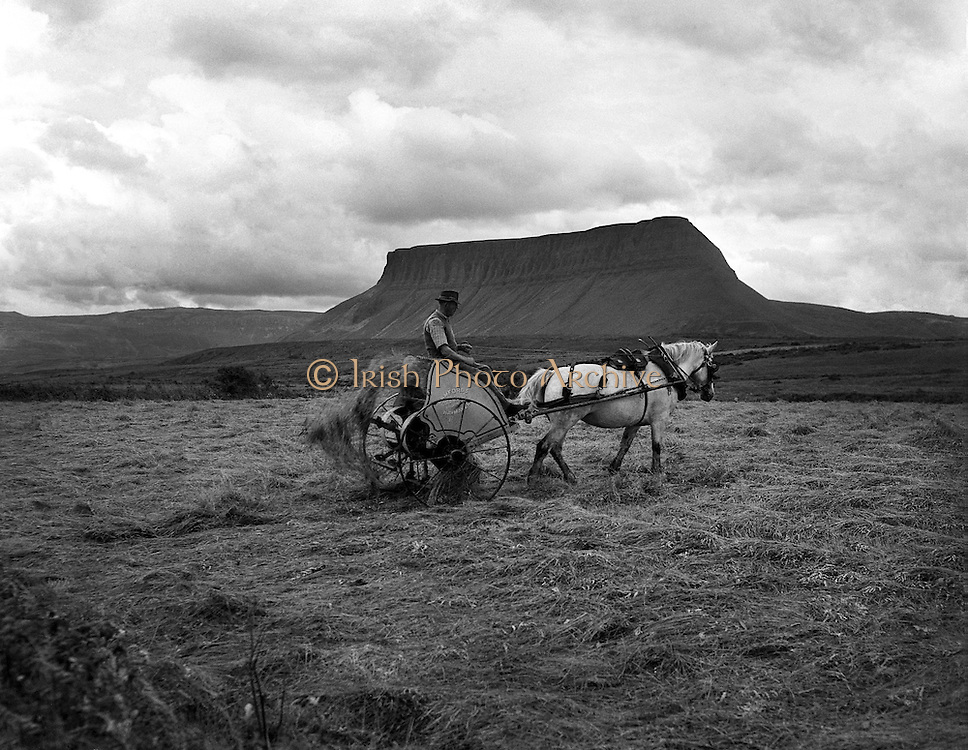 "Views - Ben Bulben, Co. Sligo.25/04/1957..Ben Bulben, sometimes spelt Benbulben or Benbulbin (from the Irish: Binn Ghulbain), is a large rock formation in County Sligo, Ireland. It is part of the Dartry Mountains, an area sometimes called ""Yeats Country""..Ben Bulben is listed as a protected structure..""Ben Bulben"", ""Benbulben"", and ""Benbulbin"" are all anglicizations of the Irish name ""Binn Ghulbain"". ""Binn"" is the word most often used for ""peak"" or ""mountain"", while ""Ghulbain"" means either ""Gulban('s)"" or ""jaw-shaped"". The two most common translations are ""Gulban's peak"" and ""jaw-shaped peak."".Ben Bulben was formed during the Ice age, when Ireland was under glaciers. Originally it was a large ridge. The moving glaciers shaped it into its present distinct formation. ."