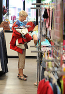 DOYLESTOWN, PA - AUGUST 23:  A woman, who declined to be identified, browses a clothing rack at the grand opening of In Full Swing, A Woman's Place's newly designed and relocated thrift shop August 23, 2014 in Doylestown, Pennsylvania. (Photo by William Thomas Cain/Cain Images)