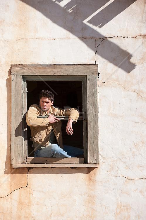 Guy sitting in a rustic rual window