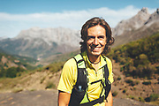 Potrait of a smiling utra trail runner looking at camera Trail runner running uphill in Collado Jermoso, Picos de Europa National Park, Spain