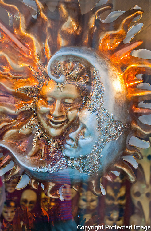 Close-up of sun and the moon carnival masks in a window in Venice, Italy.