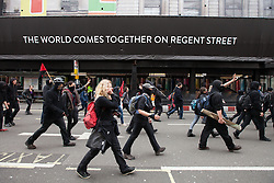 © Licensed to London News Pictures . FILE PHOTO DATED 20/10/2012 of a Black Bloc of protesters breaking away from a TUC demonstration on Regent Street in London , as reports circulate that black bloc tactics may be employed by protesters seeking to demonstrate during the funeral of former British Prime Minister Margaret Thatcher . Photo credit : Joel Goodman/LNP
