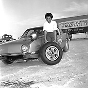 Driver Paula Murphy poses with a Halibrand wheel and Sears Allstate tire in front of the #9 Studebaker Avanti at the Bonneville Salt Flats, October, 1963.