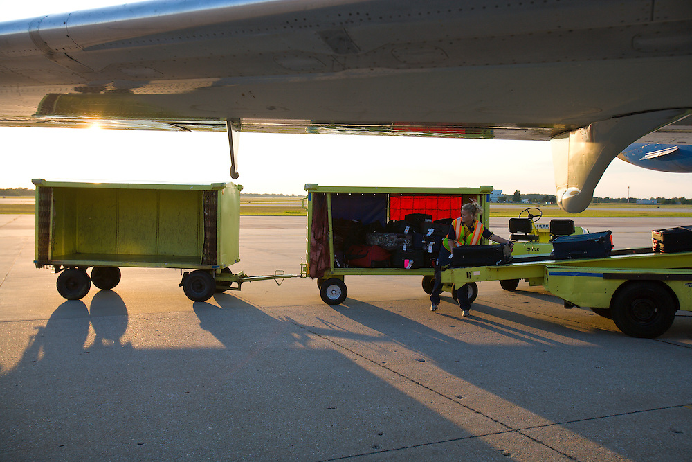 An airline employee loads luggage into a commercial jet airplane.