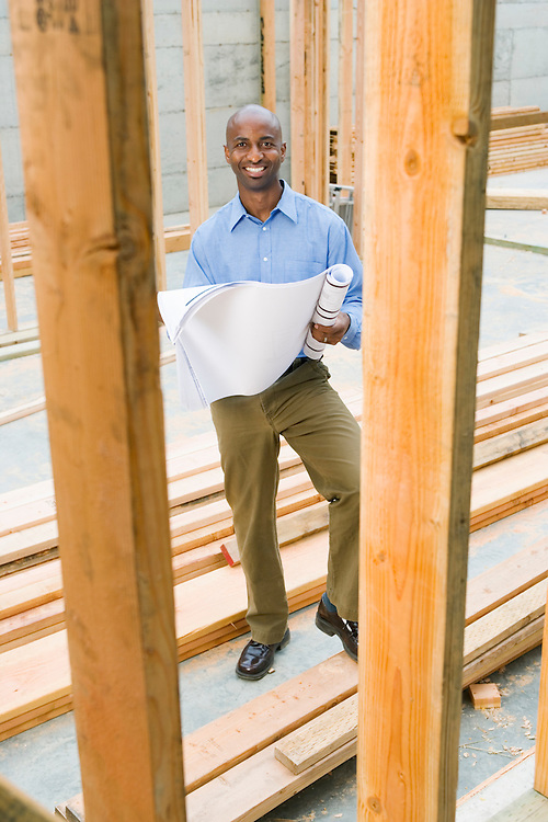 Portrait of young male professional at building site with plans.