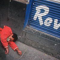 Man passed out on the street next to the shutters of a shop in the city centre..
