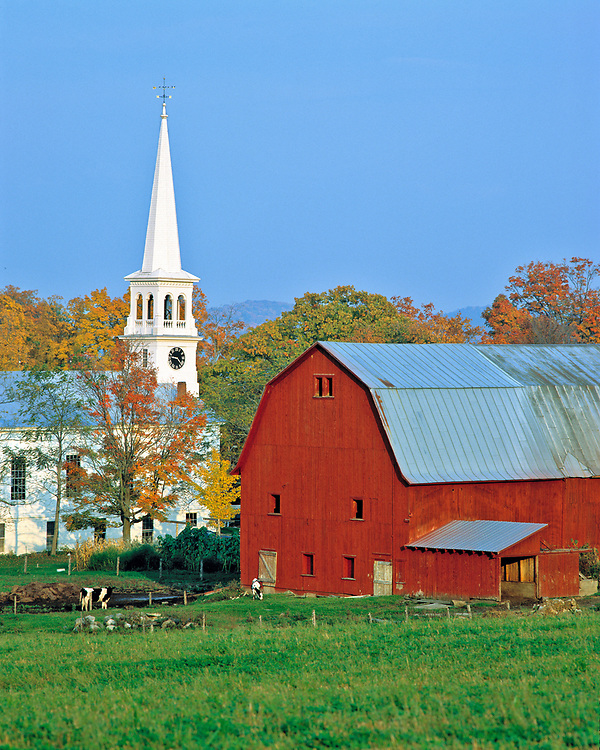 A red barn and white church contrast with the green pasture in Peacham, Vermont.