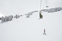 JEROME A. POLLOS/Press..A snowboarder travels under the chairlift as riders make their way to the top of the mountain.