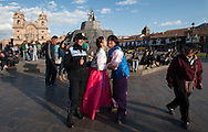 A South Korean couple on their honeymoon dress in traditional clothing of their country while visiting the Plaza Mayor of Cuzco. Despite being the city most visited by foreign tourists, No Sino-Japanese Asians, like the Indians, they are still a novelty, an opportunity for the local police, for a souvenir photo