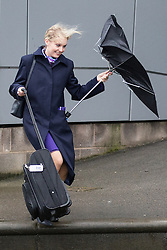 © Licensed to London News Pictures . 06/02/2016 . Birmingham , UK . A woman has her umbrella blown inside out in driving rain , as she struggles with her luggage , at Birmingham International train station . Photo credit: Joel Goodman/LNP