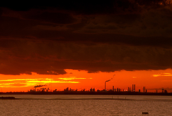 Stock photo of a silhouette view of a refinery at sunset