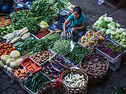 11 OCTOBER 2016 - UBUD, BALI, INDONESIA: A vendor in the morning market in Ubud. The morning market in Ubud is for produce and meat and serves local people from about 4:30 AM until about 7:30 AM. As the morning progresses the local vendors pack up and leave and vendors selling tourist curios move in. By about 8:30 AM the market is mostly a tourist market selling curios to tourists. Ubud is Bali's art and cultural center.      PHOTO BY JACK KURTZ