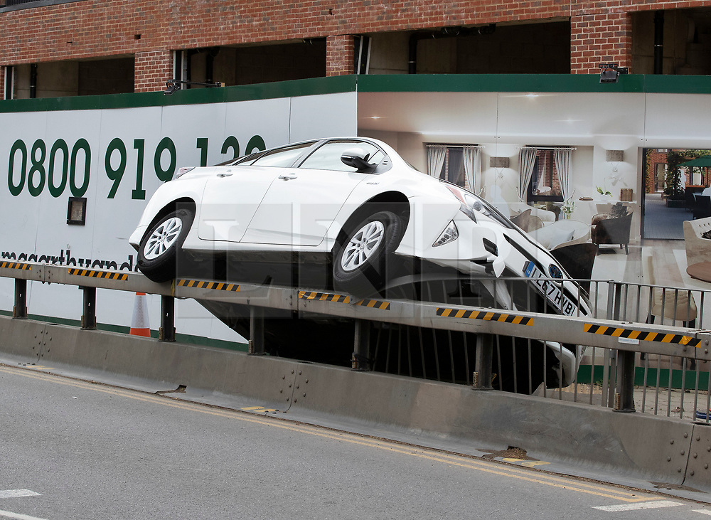 © Licensed to London News Pictures. 27/04/2019. Cobham, UK. A Toyota minicab has mounted a temporary pedestrian barrier in busy Cobham High Street in Surrey. It is unclear if the driver was affected by high winds and rain from Storm Hannah as he drove the 15-20 meters along the length of the barrier.Photo credit: Peter Macdiarmid/LNP