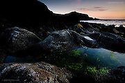The light dropped rapidly and here on the far side of the smoothed Atlantic pounded granite rock now looked dark and impassable. Deep rock pools contained small life forms darting from side to side waiting for the advancing high tide.