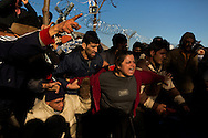 A woman screams at Greek riot police after they fired tear gas into a group of asylum seekers who gathered at a border crossing to Macedonia near Idomeni to protest recent border restrictions on December 3, 2015. Babies and small children were present in the group, many of which were severely effected by the tear gas.