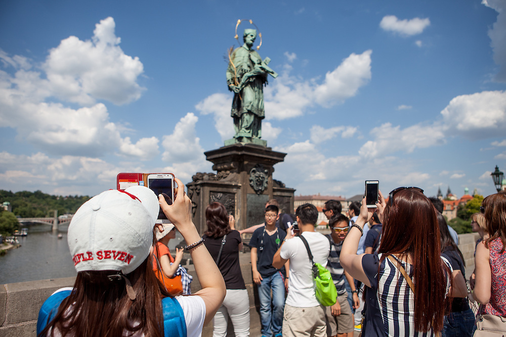 Tourists photographing with their mobile phones the St. John of Nepomuk Statue on Prague Charles Bridge.