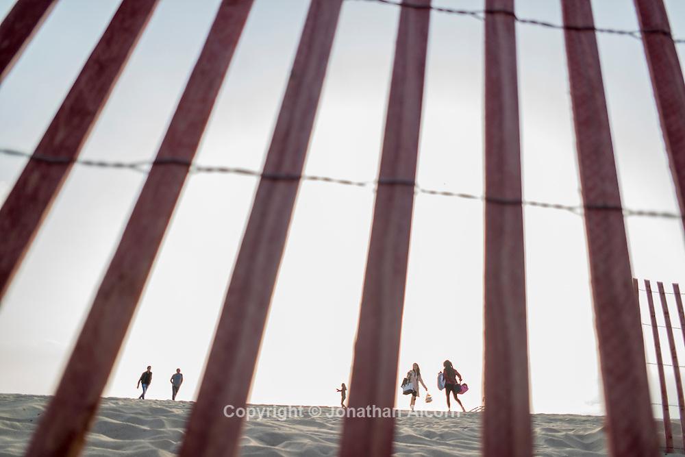 Beach goers on Santa Monica beach as seen through a sand fence