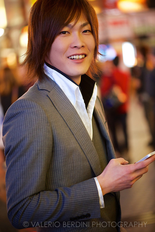 A smart dressed 'host' waits for a customer in Dotonbori . Osaka, Japan 2013