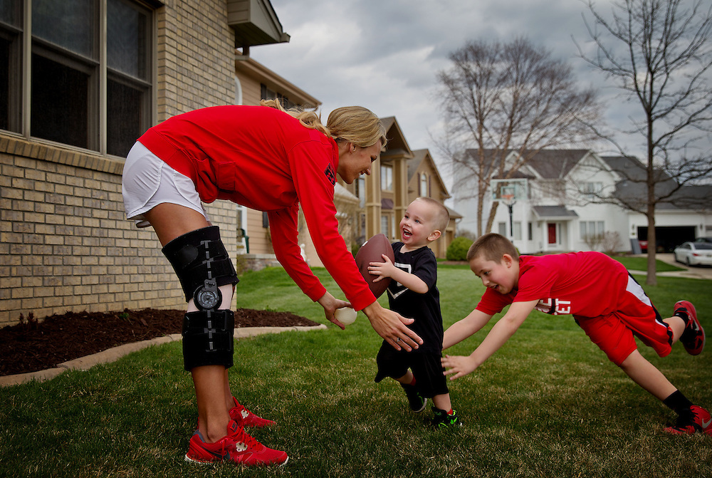 Almost two weeks after a surgery to fix a torn ACL in her right leg, Leslie Walls is back at the game with her sons Colton Walls, 2, and Noah Walls, 9, outside of their home in Omaha on Friday, April 26, 2013. &quot;These girls have worked so hard that it&rsquo;s inspiring just to even watch them. It is heart wrenching not to be on the field, but it&rsquo;s inspiring to watch from day one what they&rsquo;ve put in to where they are now,&quot; Walls said.<br />