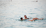 Israel, Dead Sea People float in the heavy water of the Dead Sea.