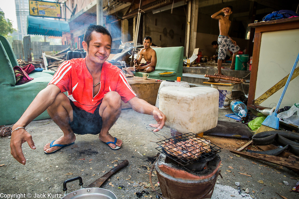 "11 DECEMBER 2012 - BANGKOK, THAILAND: A worker grills chicken in front of the empty building he lives in while he works on its demolition at ""Washington Square"" a notorious entertainment district off Sukhumvit Soi 22 in Bangkok. Demolition workers on many projects in Thailand live on their job site tearing down the building and recycling what can recycled as they do so until the site is no longer inhabitable. They sleep on the floors in the buildings or sometimes in tents, cooking on gas or charcoal stoves working from morning till dark. Sometimes families live and work together, other times just men. Washington Square was one of Bangkok's oldest red light districts. It was closed early 2012 and is being torn down to make way for redevelopment.   PHOTO BY JACK KURTZ"