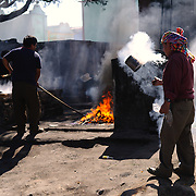 Local shaman perform a traditional K'iche' Maya ceremony using censers with smouldering incense and copal resin at a section of the town's cemetary on Chichicastengo's outskirts. Chichicastenango is an indigenous Maya town in the Guatemalan highlands about 90 miles northwest of Guatemala City and at an elevation of nearly 6,500 feet. It is most famous for its markets on Sundays and Thursdays.