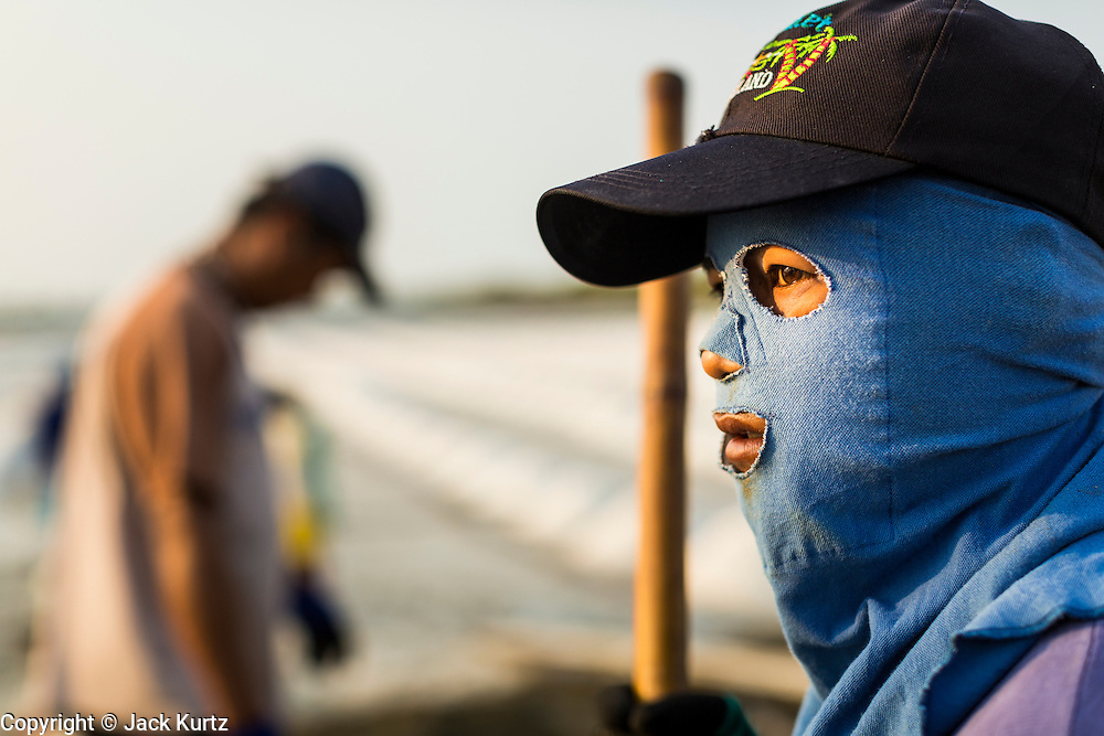 "28 MARCH 2014 - NA KHOK, SAMUT SAKHON, THAILAND: A salt worker near an evaporation pond in Samut Sakon province. Workers cover their bodies to protect them from the sun and briney water they stand in all day. Thai salt farmers south of Bangkok are experiencing a better than usual year this year because of the drought gripping Thailand. Some salt farmers say they could get an extra month of salt collection out of their fields because it has rained so little through the current dry season. Salt is normally collected from late February through May. Fields are flooded with sea water and salt is collected as the water evaporates. Last year, the salt season was shortened by more than a month because of unseasonable rains. The Thai government has warned farmers and consumers that 2014 may be a record dry year because an expected ""El Nino"" weather pattern will block rain in mainland Southeast Asia. Salt has traditionally been harvested in tidal basins along the coast southwest of Bangkok but industrial development in the area has reduced the amount of land available for commercial salt production and now salt is mainly harvested in a small parts of Samut Songkhram and Samut Sakhon provinces.    PHOTO BY JACK KURTZ"