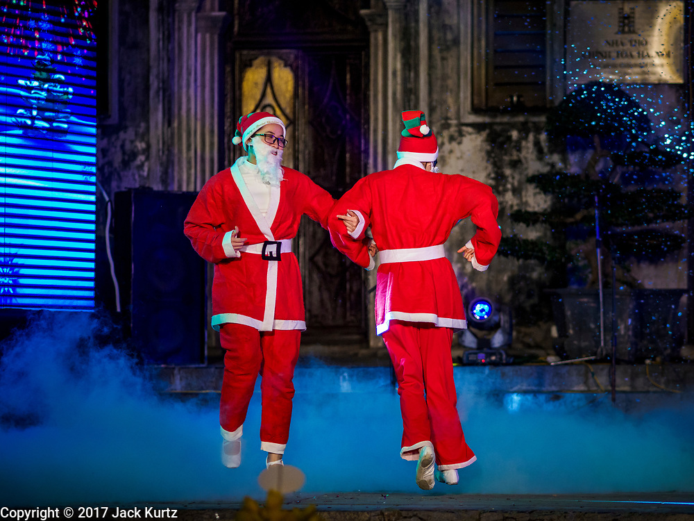 22 DECEMBER 2017 - HANOI, VIETNAM: Santa Clauses dance during the Christmas show at St. Joseph's Cathedral in Hanoi. There are about 5.6 million Catholics in Vietnam. The Cathedral was one of the first structures built by the French during the colonial era and was opened in 1886. It's one of the most popular tourist attractions in Hanoi.    PHOTO BY JACK KURTZ