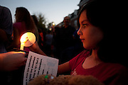 Kamilla Anderson lights a candle with the help of her mother Sonja Anderson during the candlelight vigil held?in front of the Islamic Center at the end of the Interfaith Walk. participants lit candles, observed a moment of silence and sang a song promoting love and unity between faiths.  Photo by: Ross Brinkerhoff