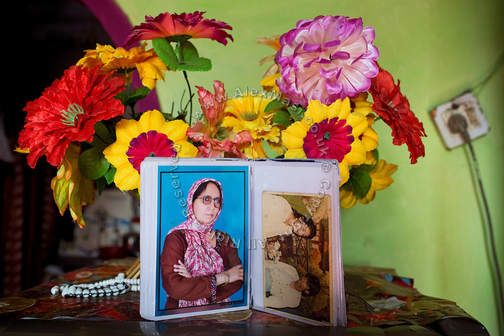 A photo album with a picture of a young Kameeza Bee, now 60, a widow 'gas-survivor' now suffering from cancer, is open near plastic flowers adorning her living room in Nawab, one of the water-affected colonies near the abandoned Union Carbide (now DOW Chemical) industrial complex in Bhopal, Madhya Pradesh, India. Kameeza and her family fed on contaminated underground water until 2010, when some pipeline was installed reached her home.