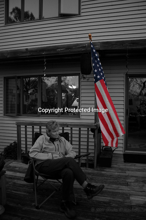 An old woman sitting on the deck with american flag in color for a color splash