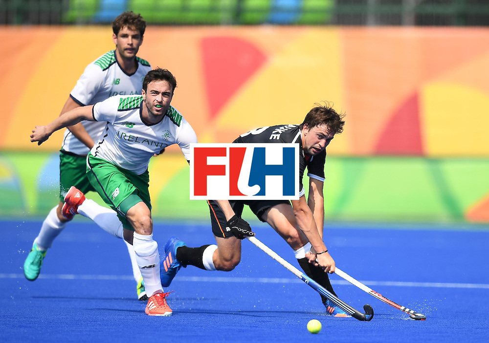 Ireland's Chris Cargo (L) stretches for the ball with Germany's Tobias Hauke during the men's field hockey Germany vs Ireland match of the Rio 2016 Olympics Games at the Olympic Hockey Centre in Rio de Janeiro on August, 9 2016. / AFP / MANAN VATSYAYANA        (Photo credit should read MANAN VATSYAYANA/AFP/Getty Images)