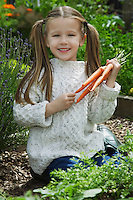 Girl (5-6) holding carrots in garden portrait