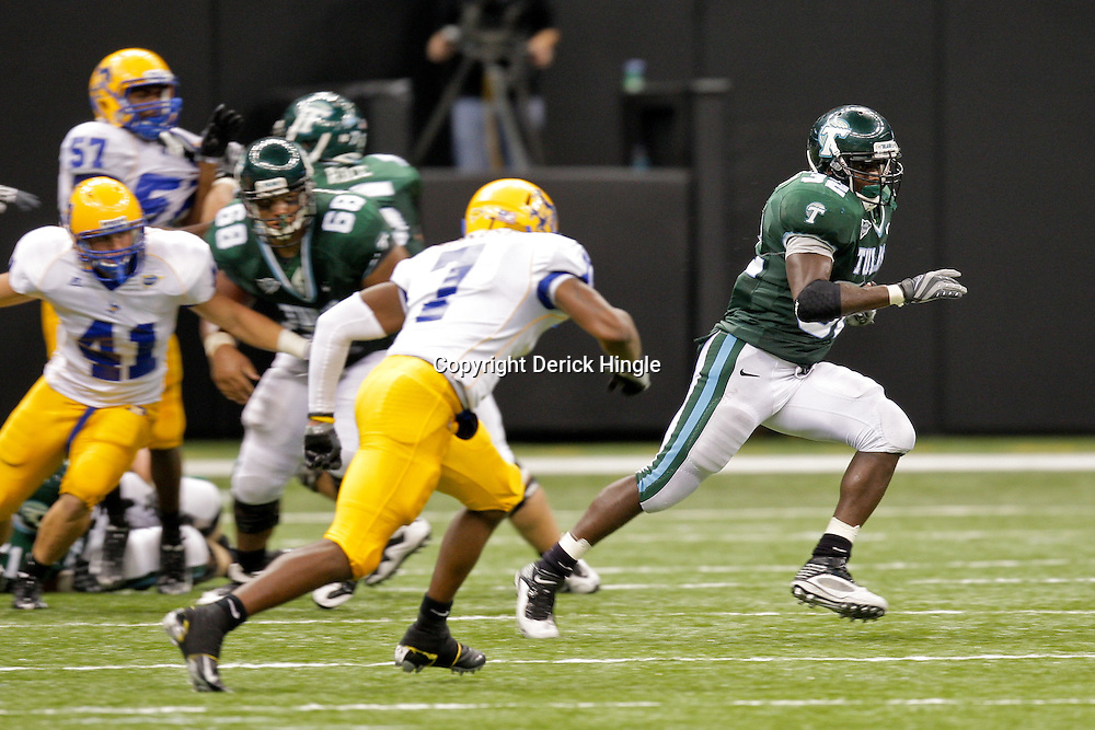 Sep 26, 2009; New Orleans, LA, USA;  Tulane Green Wave running back Andre Anderson (32) runs by McNesse State Cowboys safety Brandon Robinson (7) at the Louisiana Superdome. Tulane defeated McNeese State 42-32. Mandatory Credit: Derick E. Hingle-US PRESSWIRE