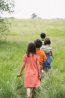 Children (7-9) walking in field