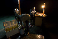 Fishermen clean their catch on a dock at Hotel La Pesca in La Pesca, Mexico. The two older men are petroleum workers from Monterrey; the younger man works at the hotel.