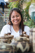Lea Delos Reyas  sells local crafts such as weaved baskets made by the Iriya tribe, Mindoro's indigenous people, in Puerto Galera, the Philippines.
