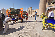 Uzbekistan, Khiva. Kultlimurodinok Medressa. Souvenir photographer with tiger for tourists.