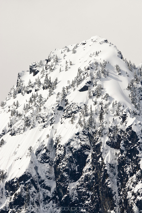 The precipitous north face of 5991 ft. Mount Index in winter snow is located on the west side of the Cascade Mountain Range in the Mt Baker-Snoqualmie National Forest just south of the Skykomish River in Washington, USA.