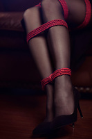 Artistic closeup of beautiful sexy woman legs in black stockings and high heel shoes with red bondage rope tied around ankles Sensual erotic body parts
