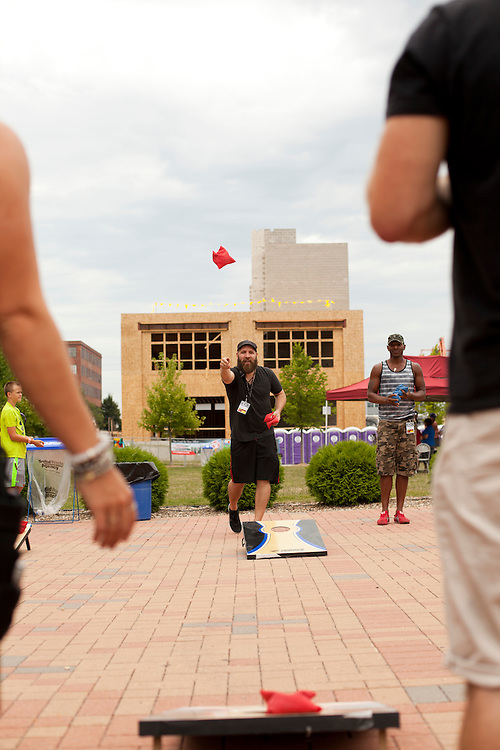 Eric Loux and Jason Holt play a game of bean bags at the NewBo Music Fest in downtown Cedar Rapids on Saturday, August 8, 2015. Loux is Allen Stone's tour manager and Holt is the band's drummer. (Rebecca F. Miller/Freelance for the Gazette)