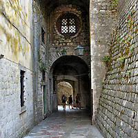 Passageway to Gurdić Gate in Kotor, Montenegro <br /> This narrow and high stone passageway leads through the Gurdić Bastion which was built in 1470. Just beyond that archway is the Vrata od Gurdića or South Gate. It is the oldest of the three city's portals. It was initially constructed in the 9th century. The current version is from the 13th century.  From there you can take a wooden drawbridge over a small pool of water called the Gurdić spring. This will lead you outside of the fortified town and back to the harbor. But there is so much more of Stari Grad to see. So turn around and head back into Old Town.