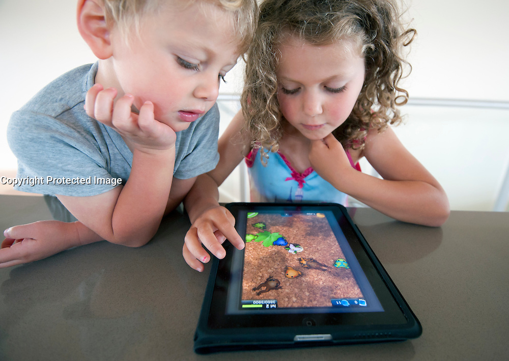 Children playing computer game on an iPad tablet computer