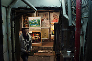 For a story by Dan Levin slug Hong Kong.February 12 2013, Kowloon, Hong Kong.An African visitor to the Chungking Mansions getting into the building through a side alley where paintings are on sale..Credit: Gilles Sabrie for The New York Times..