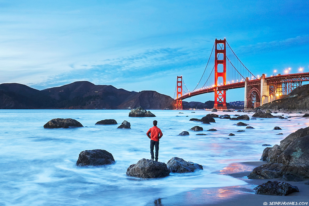 A man stands on a rock at Marshall's Beach admiring the Golden Gate Bridge in San Francisco, California.