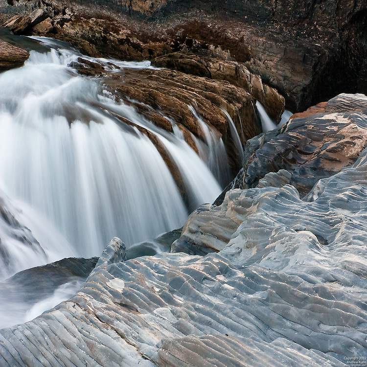 Close-up views of the water of the Kicking Horse River cascading into a crevice at the Natural Bridge in the fall when water flows are low.
