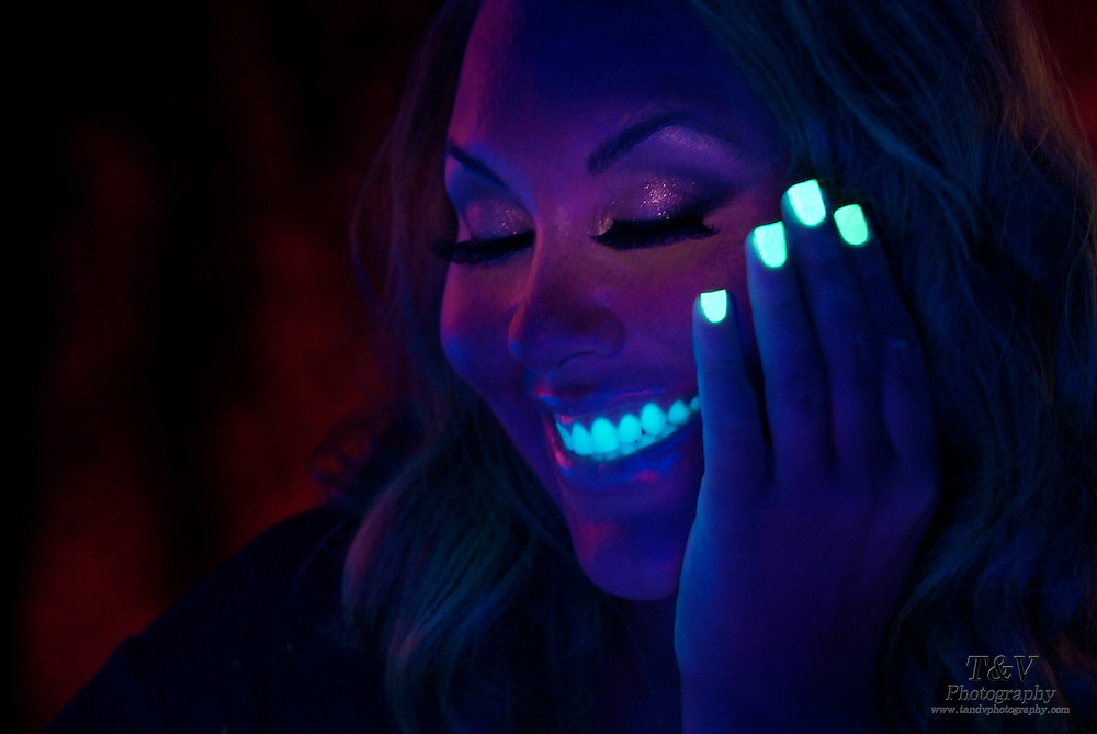 Smiling woman with glowing fingernails and teeth.Black light