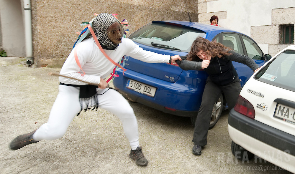 A momotxorro grabs a woman during the ancient carnival of Unanu, North of Navarra province in Spain, on March 8, 2011. Momotxorros chase locals and slash them with sticks.  PHOTO/ RAFA RIVAS