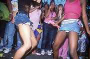A crowd wayching two girls dancing with extremely short denim skirts, Notting Hill Carnival, London, UK 2004